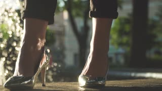 Woman in elegant silver shoes standing near fountain