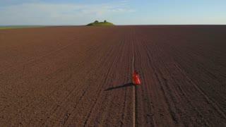 Woman in long red dress walks on plowed field