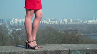 Woman in red skirt and in shoes on heels stand at blurred city background