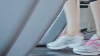 Woman in sneakers run on treadmill