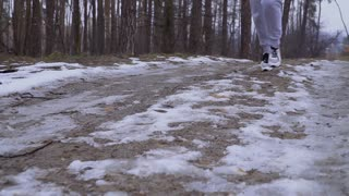 Woman in snickers runs along snow road in slowmotion