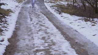 Woman in sportswear runs along snow road in slowmotion