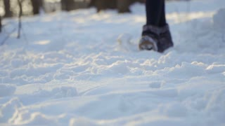 Woman in winter boots walk on snow in slow motion