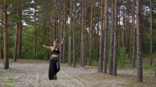 Woman is dancing tribal dance in the forest