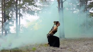 Woman is dancing tribal dance in the pillar of blue smoke