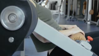 Woman makes pushes for buttocks on training apparatus