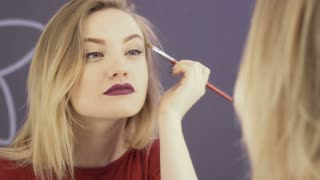 Woman makes up her eyes in front of mirror