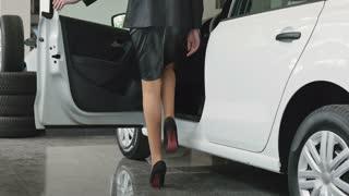 Woman on high heels sits inside a luxury car