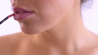 Woman paint lips with pink lipgloss