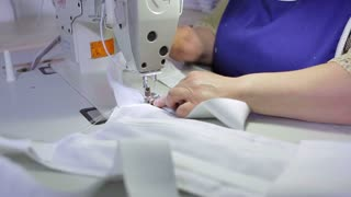 Woman sews white product on the sewing machine