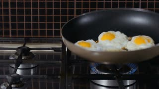 Woman shakes scrumbled eggs on the frying pan