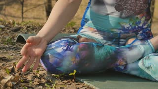 Woman sits in lotus pose and meditating