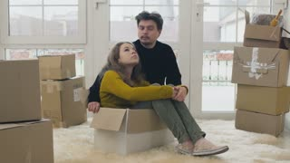 Woman sits inside of box and discuss with husband a new life in new house