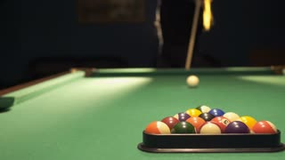 Woman stands near billiard table with cue in hands