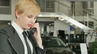 Woman talking on the phone in car showroom