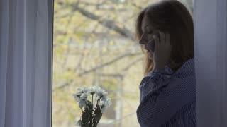 Woman talks on the phone near the window