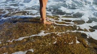 Woman touches the seaweed standing on the stone