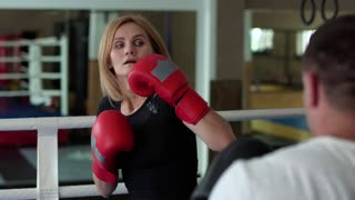 Woman training kickboxing hits with leg with trainer at boxing ring