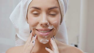 Woman washes her face with gel for facial washing in slowmotion