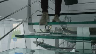 Woman with bag goes down the glass stairs
