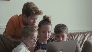 Woman with little sons watches movie on laptop at home