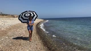 Woman with umbrella walks at seashore