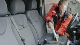Worker clean cabin of car with vacuum cleaner