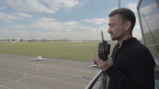 Worker of airport use binoculars and portable radio standing in control tower