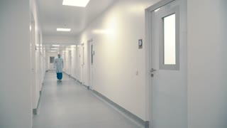Worker of hospital walk through corridor into one of the rooms