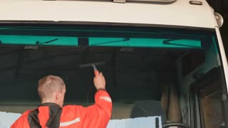 Worker removes remains of water from windshield of truck