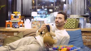 Young adult man plays with soft toy dog in children's room in cafe