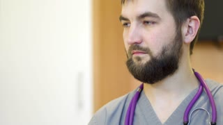 Young bearded doctor in hospital room