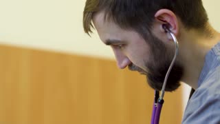 Young bearded doctor listen heartbeating of patieent with stethoscope
