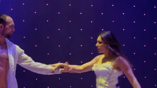 Young beautiful couple are dancing sensual dance on the stage in theatre