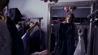 Young beautiful girl looks at the mirror and choosing clothes for special event