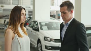 Young beautiful woman buys a car into car dealership