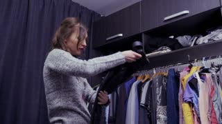 Young beautiful woman chooses clothes for special event in her dressing room