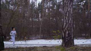 Young beautiful woman runs in winter forest in slowmotion