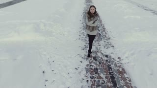 Young brunette is walking on winter road