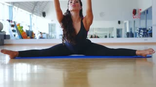 Young brunette training her flexibility in cross split on the mat in the gym