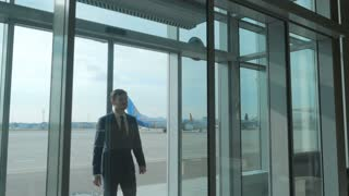 Young businessman enters the airport building