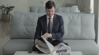 Young businessman is reading a newspaper and waits the boarding on the plane