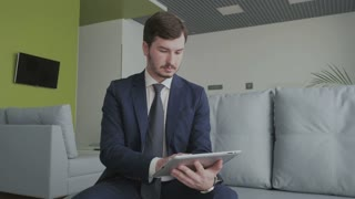 Young businessman uses a tablet in a vip lounge hall in the airport