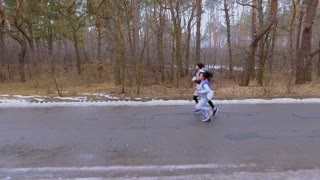 Young caucasian friends runs along road in the forest in slowmotion