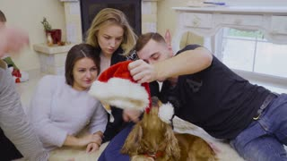 Young caucasian guys and girls relax on floor at home and have fun with dog