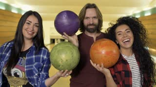 Young caucasian people have fun with bowling balls