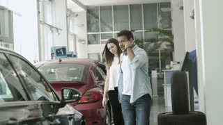Young couple arguing and choose the car in car dealership