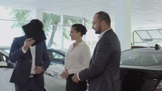 Young couple is buying a new car in the car dealership