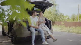 Young couple relax sitting inside the trunk of electric car