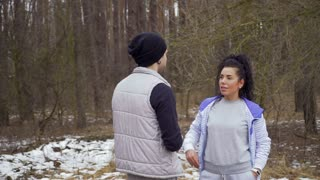 Young couple talks in winter forest and restores their forces after training